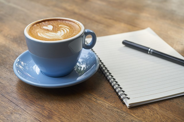 A blank notebook and pen next to a cup of coffee with decorated latte art.